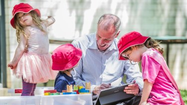 Professor Tom Lowrie of the University of Canberra's STEM Education Research Centre plays with children from the Wiradjuri Pre-school.