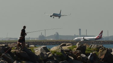 Two men fishing at Botany Bay as planes come into land and prepare to take off at Sydney Airport.