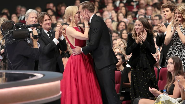 Nicole Kidman congratulates her co-star Alexander Skarsgard with a kiss on the lips at the Emmys while husband Keith Urban claps his congratulations.