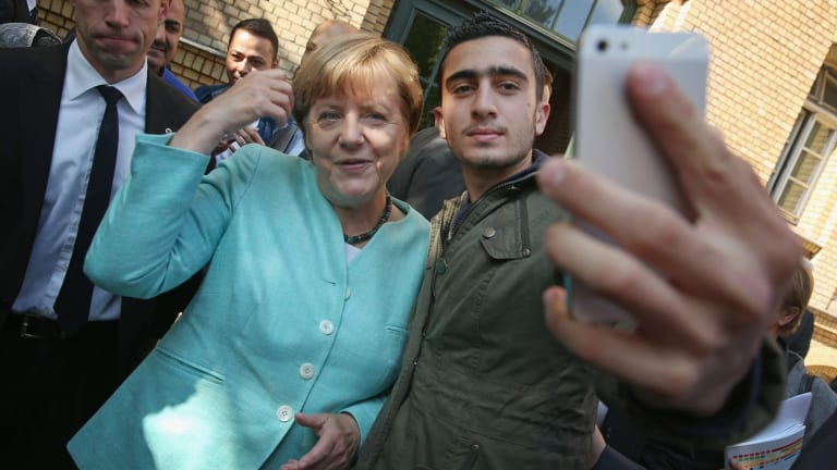 Angela Merkel poses for a selfie with a migrant from Syria. Germany offered a haven for Syrian refugees to ease Europe's migration crisis.