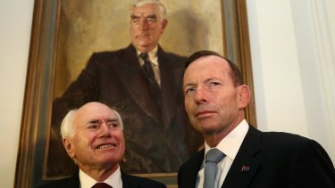 Former prime minister John Howard (left) and Prime Minister Tony Abbott stand before a portrait of their political predecessor Robert Menzies.