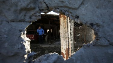 Shelling continues: A man is seen through a damaged wall in Donetsk.