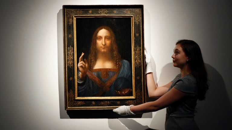 An employee with Leonardo da Vinci's Salvator Mundi on display at Christie's auction rooms, in London, before the auction.
