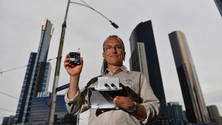 EPA expert Dr Anthony Boxshall holds a small air quality sensor, now installed on Queens Street Bridge lamps.
