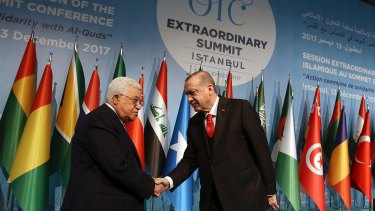 Turkish President Recep Tayyip Erdogan, right, shakes hands with Palestinian President Mahmoud Abbas.