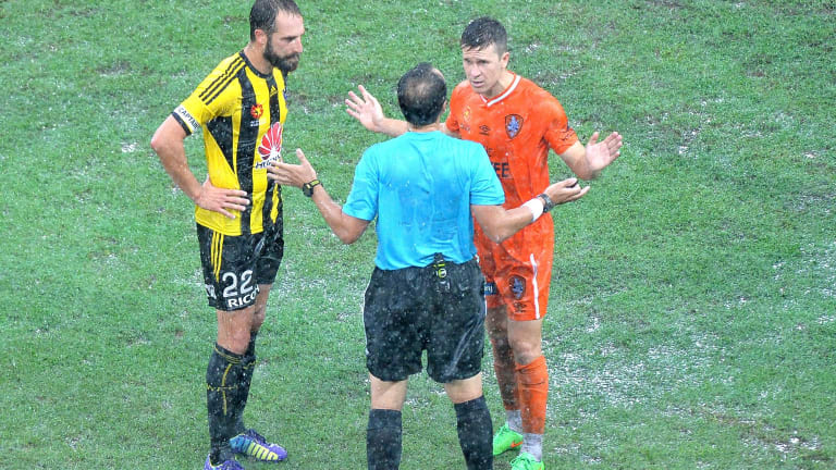 Roar captain Matt McKay debates with referee Alan Milliner after the match against Wellington Phoenix at Suncorp Stadium was called off due to heavy rain.