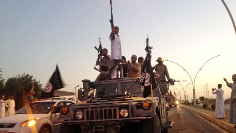Arrival: Islamic State fighters parade through Mosul in a commandeered Iraqi security forces armoured vehicle in June.