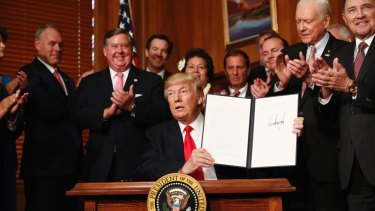 President Donald Trump holds up the signed executive order in Washington on Wednesday.
