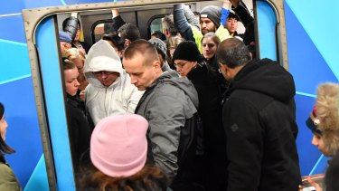 Passengers try to squeeze aboard a packed train during Thursday's rail meltdown.