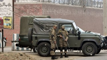 Pakistani soldiers stand guard outside the Faisalabad prison as an execution of convicted militants takes place.