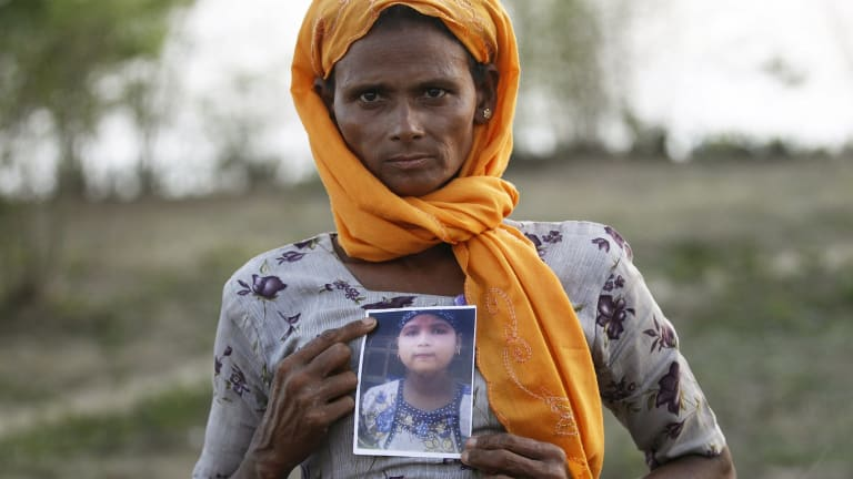 A Rohingya Muslim woman in Myanmar with a picture of her daughter, who she says is being held by a human trafficker.