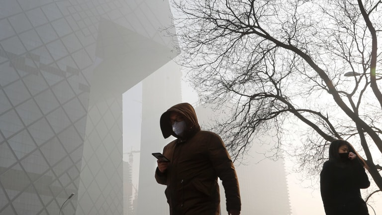 People wearing protection masks walk near the iconic headquarters of China's state broadcaster Central China Television in Beijing on Tuesday.