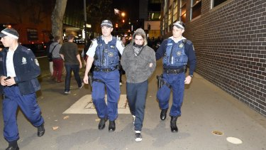 A man is arrested outside the ABC's headquarters in Ultimo on Monday night, in demonstrations for and against Pauline Hanson.