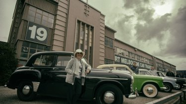 Margaret McKay rests on her 1951 Hillman Minx sedan in front of the old factory at 19 Salmon Street.