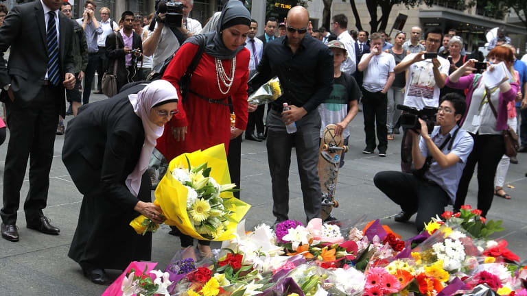 Opposing terror: Members of the Muslim community lay flowers in Martin Place, Sydney, after two people and a gunman died in a siege in December last year.