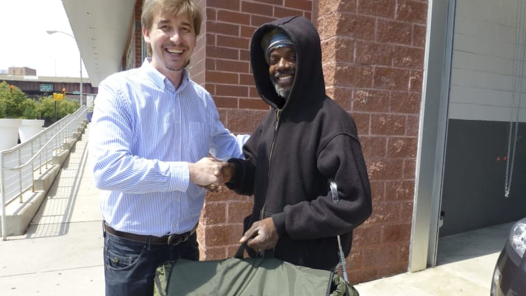 Tony Clark hands over a swag bed in a backpack to a homeless man.