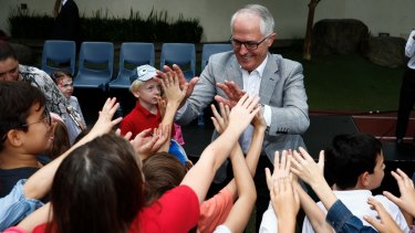Prime Minister Malcolm Turnbull gives high-fives to children during his visit to the Australian International School in Hong Kong.