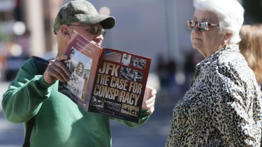 A newsagent in Dealey Plaza, Dallas, shows a magazine to a tourist on Wednesday.