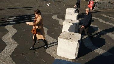 Pedestrians pass bollards in Queensbridge Square on Friday.
