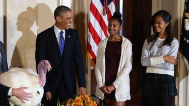 "President Obama ""pardons the turkeys"" with his daughters Sasha and Malia."