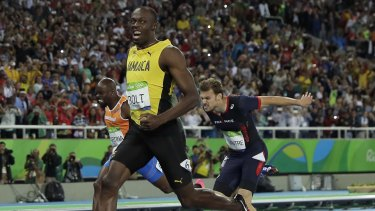 Bolt smiles as he crosses the line in Rio.
