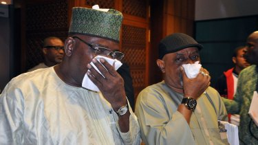 Nigerian parliament members take cover from teargas fired by police in Abuja.
