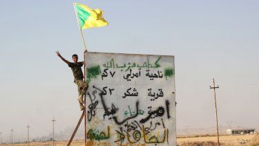 A member of Iraq's Hezbollah Brigades holds the Shiite militia's flag above a sign seven kilometres from the Iraqi town of Amerli in September, after Shiite militias helped break Islamic State's siege of the town.