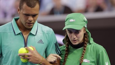 Jo-Wilfried Tsonga helps injured ballgirl Giuliana off the court at last year's Australian Open.