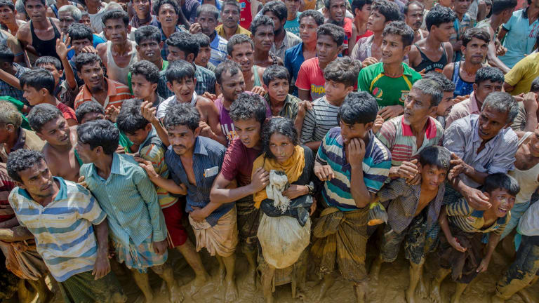 Rohingya Muslims, who crossed over from Myanmar into Bangladesh, wait to receive handouts near Balukhali refugee camp on Thursday.
