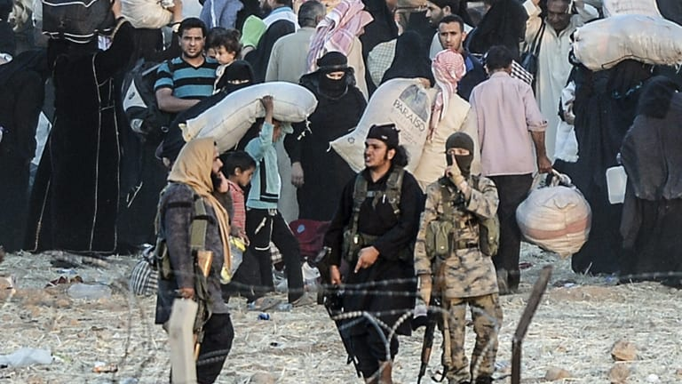 Islamic State fighters seek to return fleeing Syrians to the town of Tal Abyad.