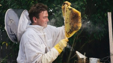 Cormac Farrell at his home in Evatt with one of the beehives he will be moving to Parliament House.