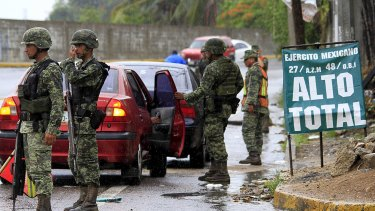 Soldiers inspect a vehicle at a checkpoint in Acapulco, Mexico on Sunday after news of El Chapo's escape.