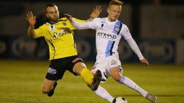 Reuben Way of Heidelberg United and Jack Clisby of Melbourne City compete for the ball.