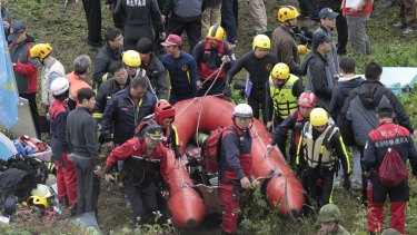Emergency personnel carry an inflatable dinghy to try to extract passengers from the plane after it crashed in a river in Taipei.