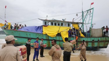 Indonesian officials load food supplies onto a boat carrying Tamil migrants stranded on the beach in Lhoknga.