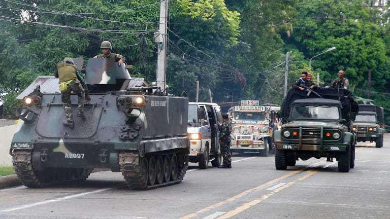 Tanks arrive at a military camp in Iligan to reinforce government troops battling Muslim militants who have laid siege to Marawi.