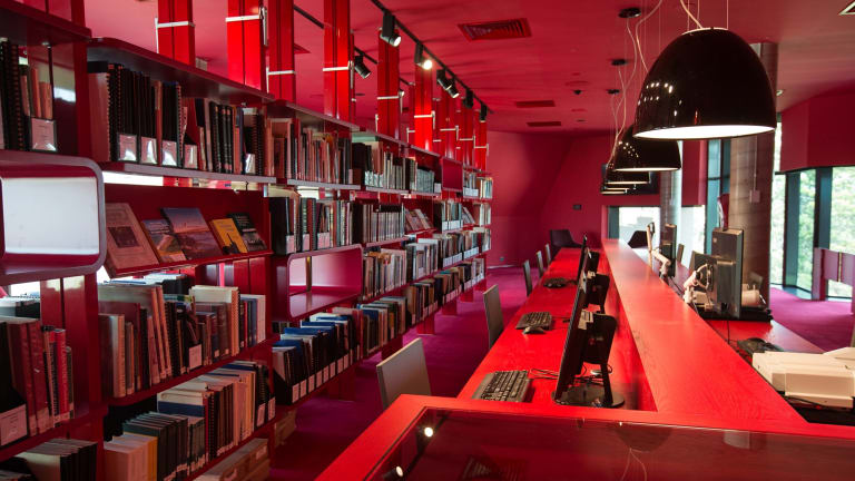 The heritage floor is decorated in bright red, with technology such as PCs, scanners and microfilm readers sitting alongside books and maps.