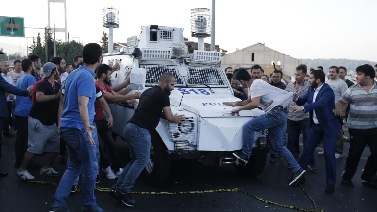 People try to stop a Turkish police armoured vehicle carrying soldiers that participated in the coup and surrendered on Saturday.
