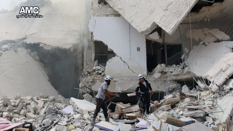 Syrian civil defence workers inspecting ruined buildings after regime air strikes in the city in August.