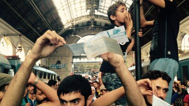 Migrants show their tickets at Budapest station, demanding to be let on a train to Germany.