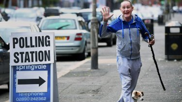 A man accompanied by his dog  makes his way into a polling station in Belfast.