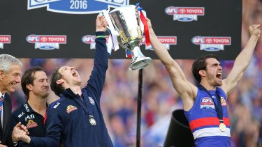 Easton Wood, Robert Murphy of the Bulldogs and Luke Beveridge, coach of the Bulldogs celebrate with the 2016 AFL Premiership Cup during the 2016 Toyota AFL Grand Final match between the Sydney Swans and the Western Bulldogs at the Melbourne Cricket Ground on October 1, 2016 in Melbourne, Australia.