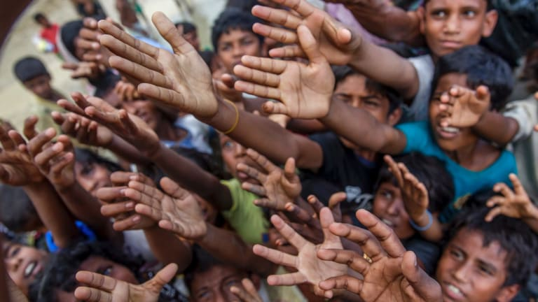 Rohingya Muslim children, who crossed over from Myanmar into Bangladesh, stretch their arms out to collect chocolates and milk distributed by Bangladeshi men at a refugee camp.