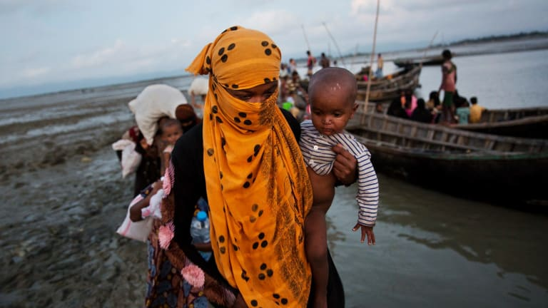 A Rohingya woman carries a child after crossing a stream on a small boat in Bangladesh after escaping violence in Myanmar.