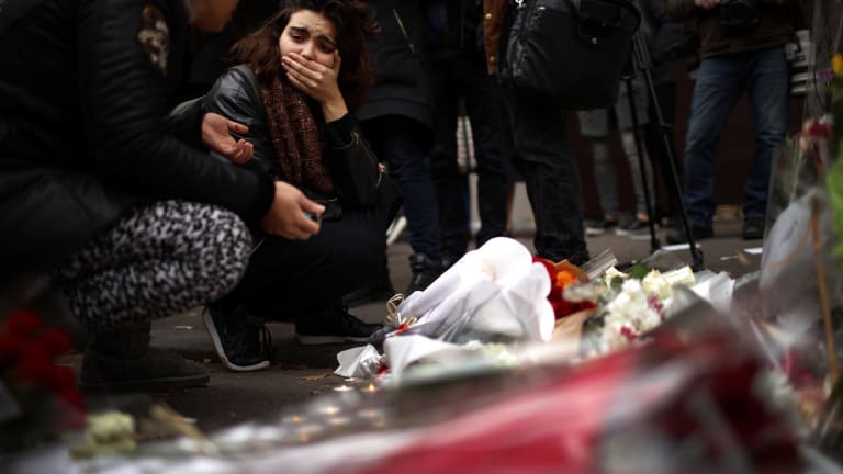 A woman places flowers near the scene of the Bataclan Theatre terrorist attack.