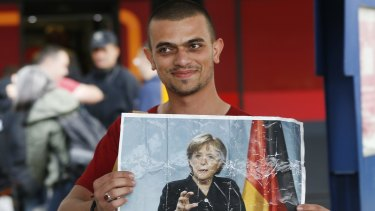 A refugee carries a picture of German Chancellor Angela Merkel as he arrives in Munich in 2015.