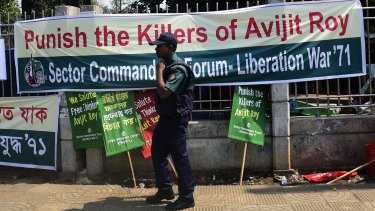 A Bangladeshi policeman walks past a banner for slain US blogger Avijit Roy during a protest in Dhaka.