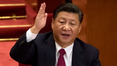 Chinese President Xi Jinping raises his hand to show approval of a work report during the closing ceremony for the 19th Party Congress