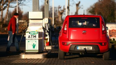 A customer returns to his Irish number-plated car at a petrol station near Newry in Northern Ireland.