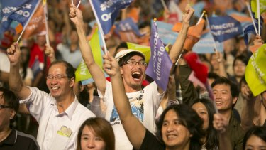 Supporters of independent opposition candidate Ko Wen-je celebrate after he won the mayoral elections for Taipei, part of a landslide defeat for Taiwan's ruling Kuomintang party.
